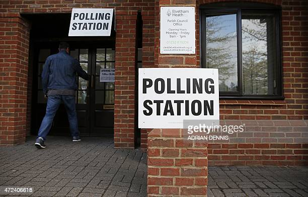 A man enters a polling station in Elvetham Heath in southern England on May 7 as Britain holds a general election Polls opened Thursday in Britain's...