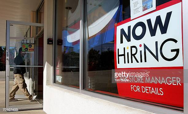 A man enters a Shoe Carnival store beyond a 'Now Hiring' sign in a window October 6 2006 in Morton Grove Illinois The US Department of Labor's...