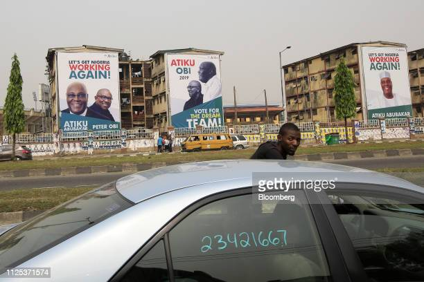 A man enters a vehicle as election posters of Atiku Abubakar candidate of the main opposition Peoples Democratic Party stand in the background in...