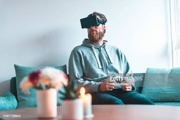 Man enters a virtual world through virtual reality headset while sitting in his living room