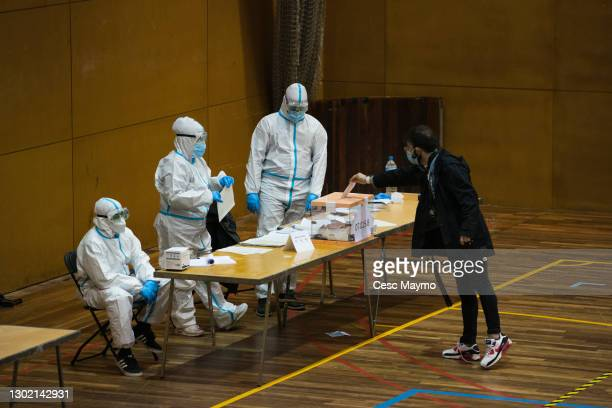 Man enters a vote in a ballot box, while poll workers are protected with PPE at CEM Guinardó during Catalonia's Regional Elections on February 14,...