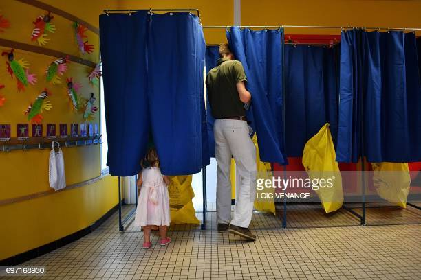 TOPSHOT A man enters a voting booth at a polling station in Nantes western France during the second round of the French parliamentary elections on...