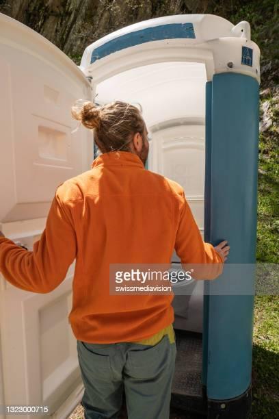 man enters portable toilet outdoors - portable information device imagens e fotografias de stock