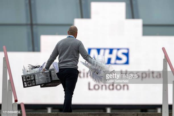 A man enters the NHS Nightingale hospital with PPE equipment at the Excel on March 30 2020 in London England The field hospital will initially...