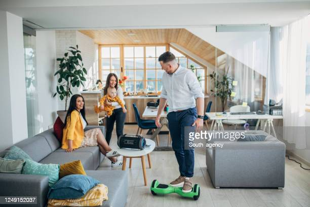 man entertaining his family while riding hoverboard in living room - hoverboard stock pictures, royalty-free photos & images