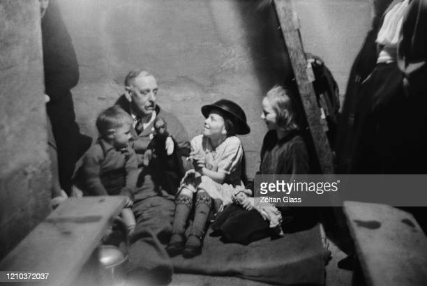 A man entertaining three children with a toy in an air raid shelter during the Blitz London October 1940 Original Publication Picture Post 308...