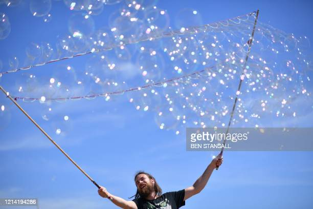 TOPSHOT A man entertains the public with bubble tricks in the sunshine on the beach in Brighton on the south coast of England on May 20 the hottest...