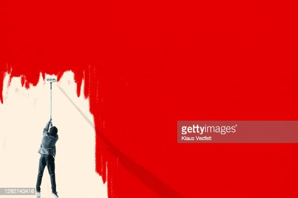 man erasing red covid-19 virus with paint roller - oresund region stock pictures, royalty-free photos & images