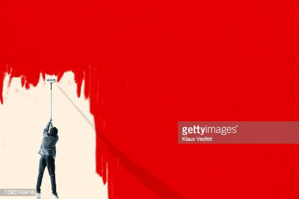 man erasing red covid-19 virus with paint roller - ausdauer stock-fotos und bilder
