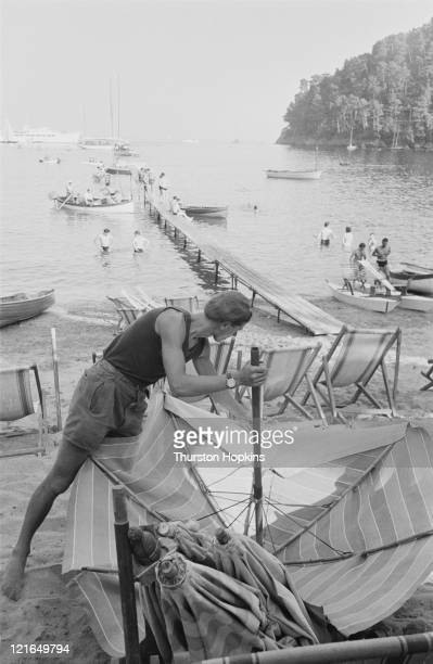 A man erects a beach umbrella on Paraggi Beach near the tourist resort of Portofino Italy August 1952 Original Publication Picture Post 6023 unpub
