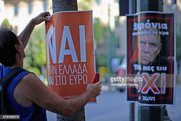 A man erects a Nai poster next to a rival Oxi poster as electioneering on the referendum continues on July 3 2015 in Athens Greece The 'Yes' and 'No'...