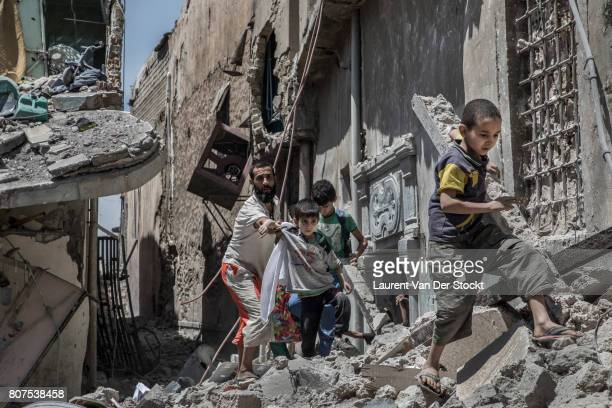 A man escorts children from a building in alNuri mosque complex on June 29 in Mosul Iraq The Iraqi Army Special Operations Forces and...