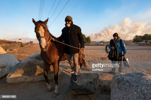 A man evacuates a horse during the Creek Fire the Shadow Hills area of Los Angeles California on December 5 2017 The raging fire fueled by strong...