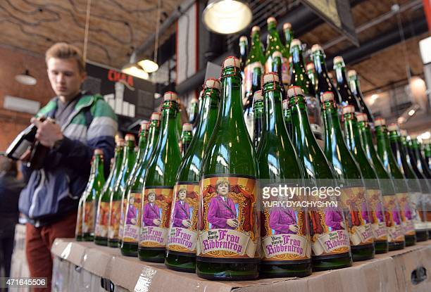 A man examines a bottle of beer from the Beer Theater restaurant and brewery called 'Frau Ribbentrop' featuring Chancellor of Germany Angela Merkel...