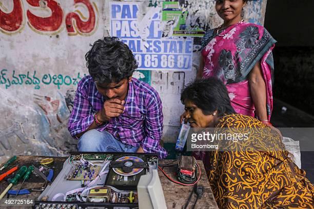 A man examines a DVD player at his roadside audio repair stall at an electronics market in Vijayawada Andhra Pradesh India on Monday Oct 12 2015...