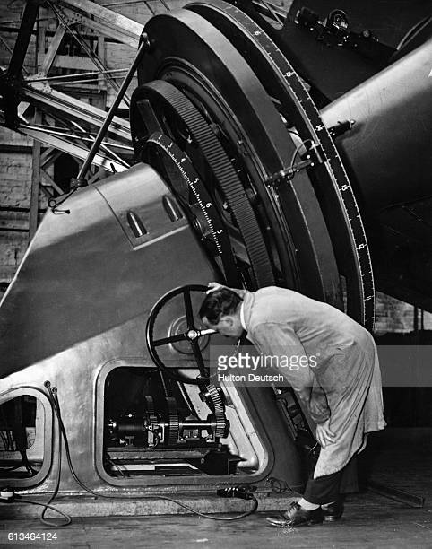 A man examines a giant telescope being assembled at the works of Sir Howard Grubb Parsons and Company in Newcastle England The telescope is for the...