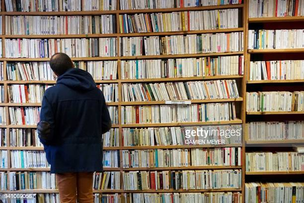 A man examines books in a bookshop on April 2 2018 during a secondhand books fair in Becherel western France / AFP PHOTO / DAMIEN MEYER