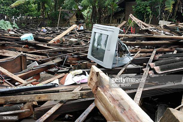 Man examines his collapsed house in Lais, 17 September 2007. The death toll from a series of major earthquakes striking Indonesia's Sumatra rose to...