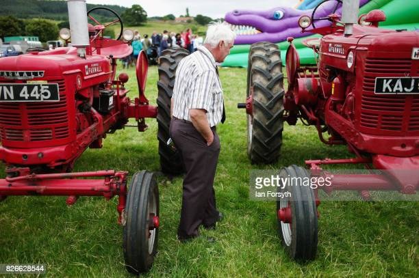 Man examines vintage tractors during the Osmotherley Country Show on August 5, 2017 in Osmotherley, England. The annual show hosts pony, cattle and...