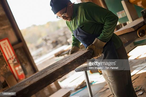Ein Mann untersuchen einen großen plank aus Holz geschnitten, in einer alten