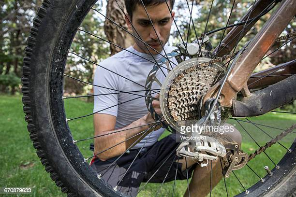 Man examining and adjusting the wheel of a mountainbike