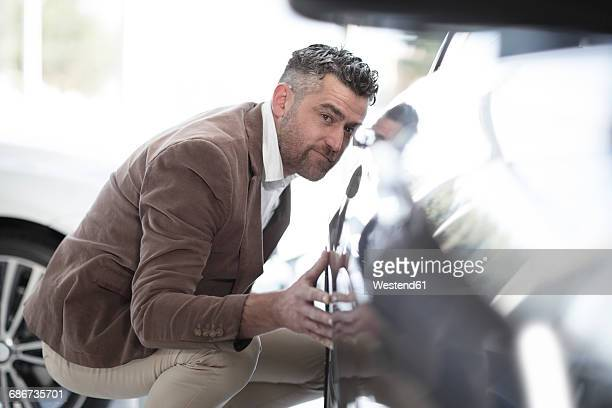 Man examining car at car dealership
