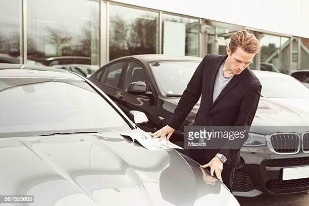 Man examining car outside showroom
