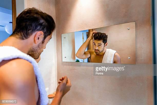 Man examining hair in mirror at bathroom at home