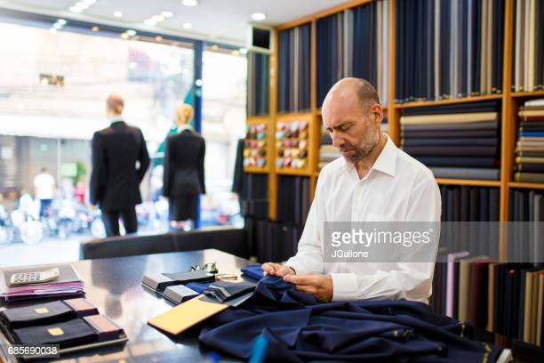 Homme en examinant des tissus de luxe dans un magasin de tailleurs
