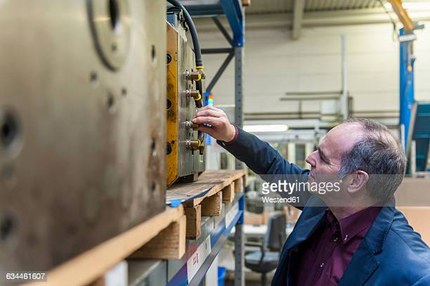 Man examining machine block in storehouse