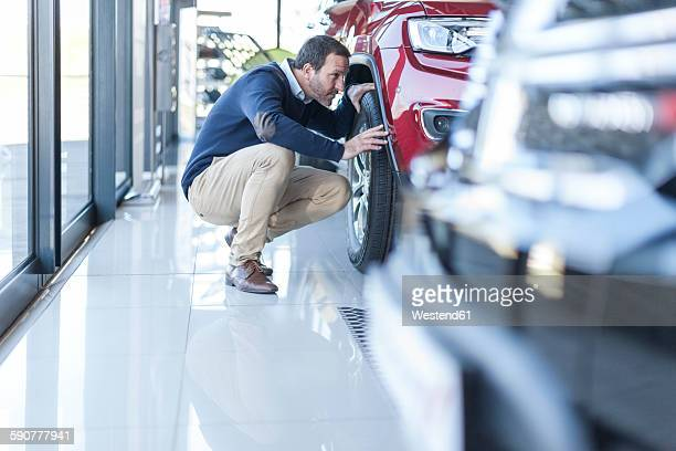 Man examining new car at car dealership