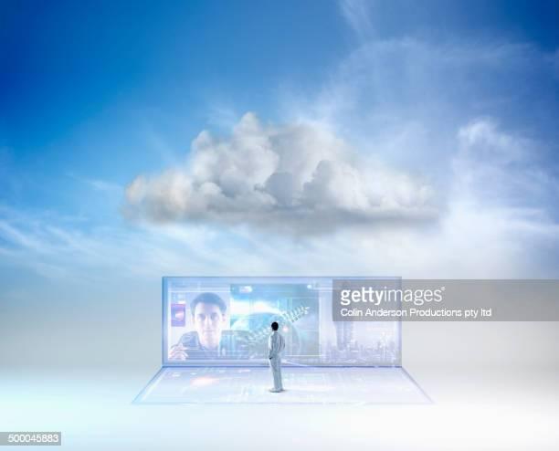 Man examining screen in blue sky