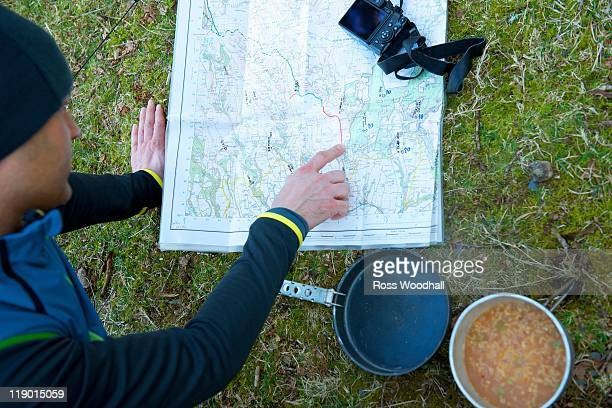 man examining trail map while camping - pointing at camera stock photos and pictures