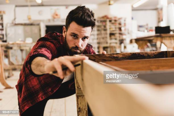 man examining wood in workshop - craftsman stock photos and pictures