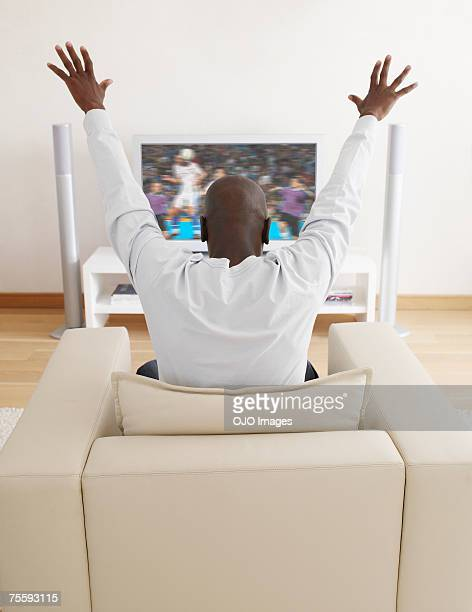 Man excitedly watching television