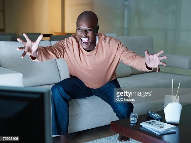 Mann excitedly vor dem Fernseher