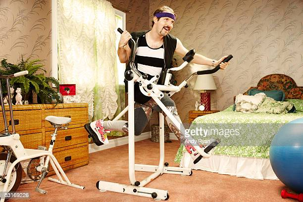man execising on vintage equipment in home gym - humor fotografías e imágenes de stock