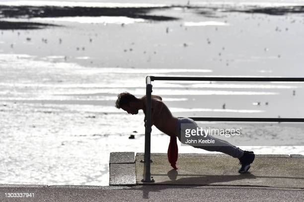 Man exercises by the beach on a warm sunny day as the weather warms for the week ahead on February 21, 2021 in Southend, England. Temperatures are...