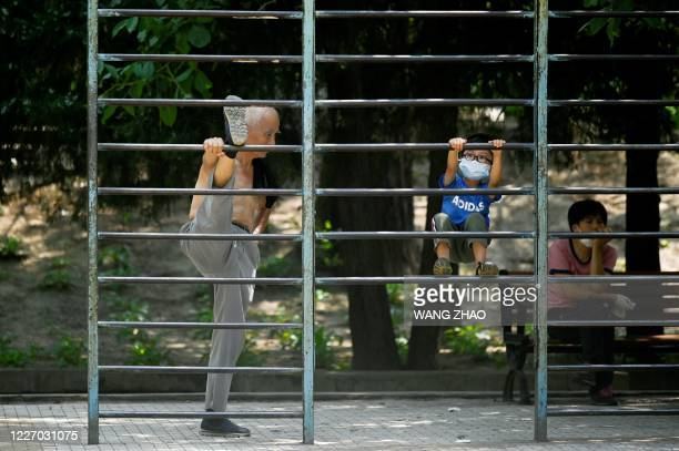 Man exercises next to a child at a park in Beijing on July 14, 2020.