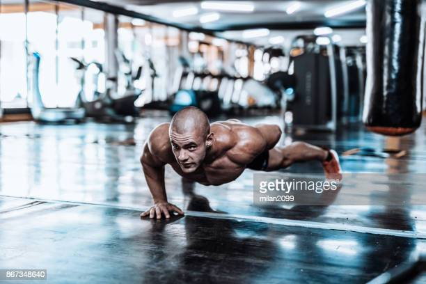 man exercising and doing push-ups in the local gym - handsome bodybuilders stock pictures, royalty-free photos & images