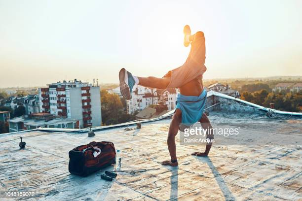 man exercising and hand standing on the rooftop - performance stock pictures, royalty-free photos & images