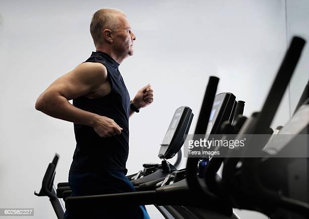 Man exercising in health club using treadmill