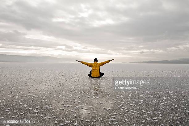Man exercising in middle of frozen lake, rear view