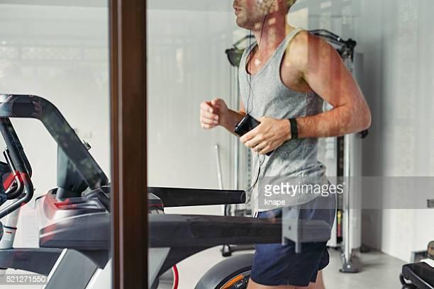 Man exercising indoors at gym running on treadmill