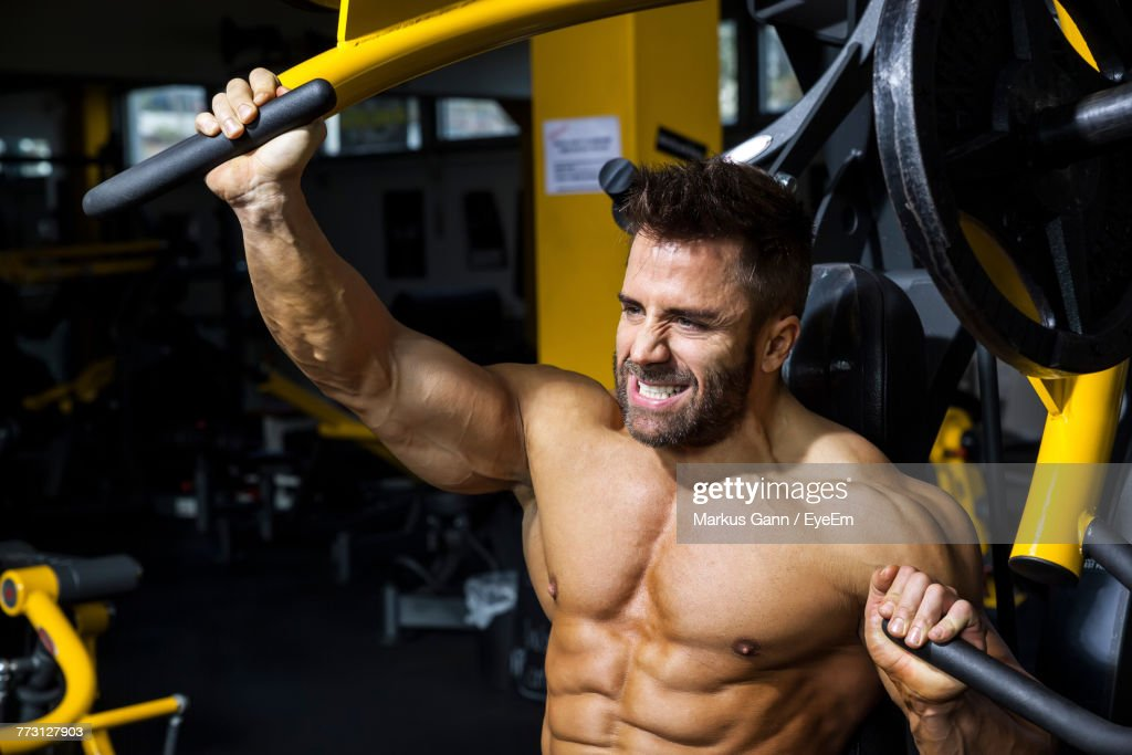 Man Exercising On Equipment At Gym : Photo