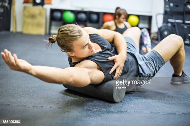 man exercising on foam roller in gym - de rola imagens e fotografias de stock