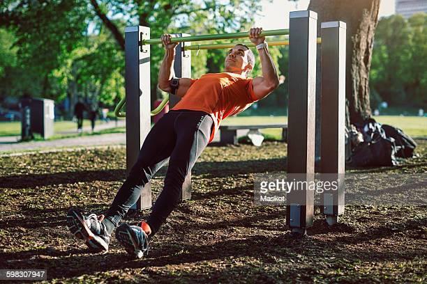 Man exercising on railing at park