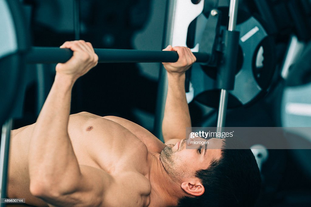Man exercising on the bench press : Stock Photo