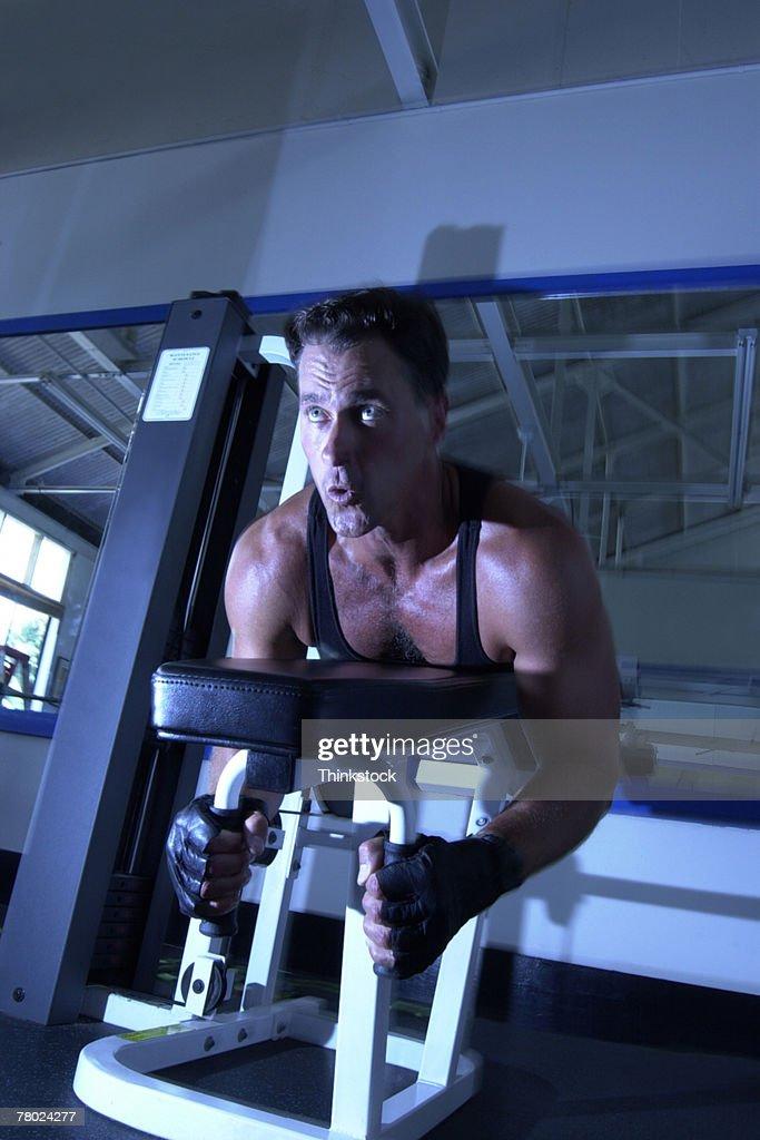 Man exercising on weight machine : Stock Photo