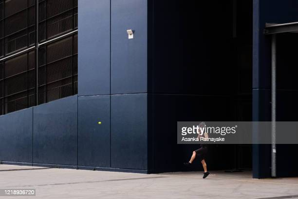 Man exercising playing tennis outside Marvel Stadium on April 15, 2020 in Melbourne, Australia. The Federal Government has closed all non-essential...